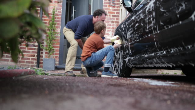 father and son washing the family car together - genderblend video stock e b–roll