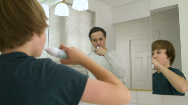 vídeos de stock, filmes e b-roll de father and son washing their teeth together - escovar dentes