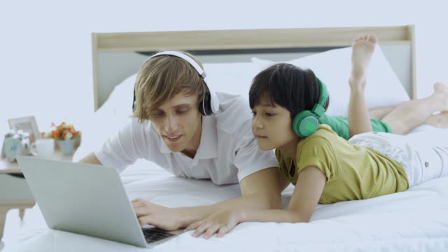 father and son watch cartoons on a laptop lying on the bed. - genderblend stock videos & royalty-free footage