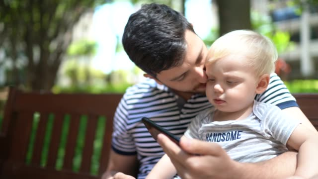 father and son watching a movie on mobile phone at park - genderblend stock videos & royalty-free footage