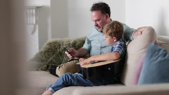 Father and Son watching a video tutorial on guitar playing