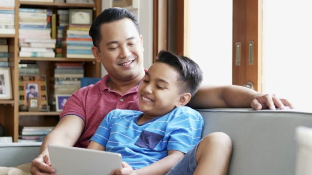 father and son watching digital tablet at home - malay family stock videos and b-roll footage