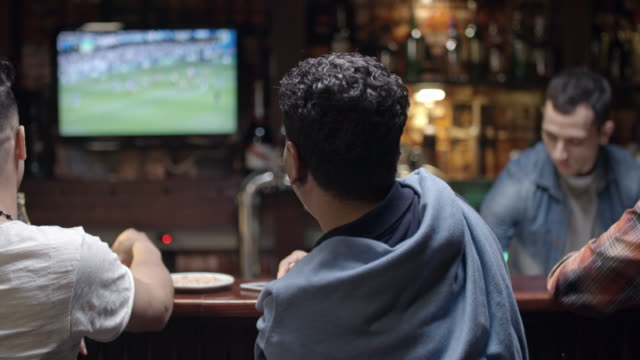 father and son watching soccer in pub - pub stock videos & royalty-free footage