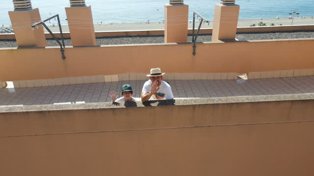 father and  son waving from a rooftop at the beach - mar stock videos & royalty-free footage