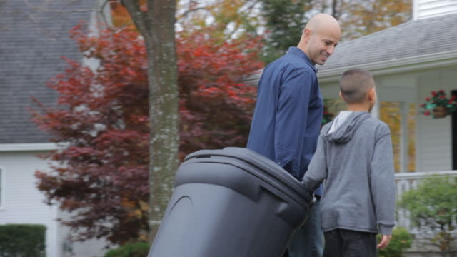 MS TS Father and son wheel in garbage can together / Albany, New York, United States