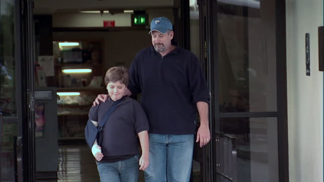 SLO MO, MS, TU, TD, Father and son (8-9) with arm in sling leaving hospital, Oroville, California, USA