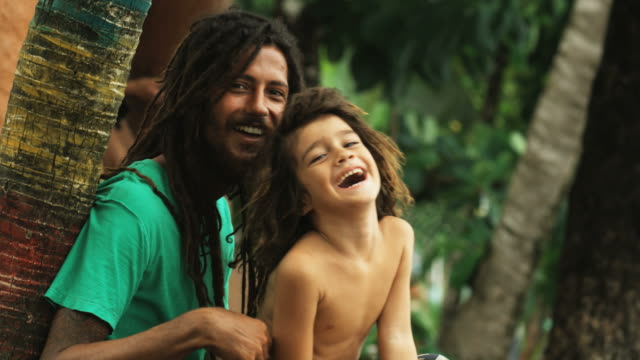 father and son with dreadlocks sitting beneath palm trees - tickling stock videos & royalty-free footage