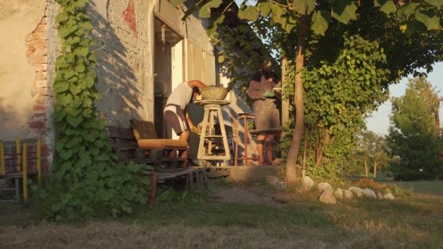 far och son arbetar framför sin verkstad i skuggan under ett träd som arbetar på något projekt - diskbänk bildbanksvideor och videomaterial från bakom kulisserna