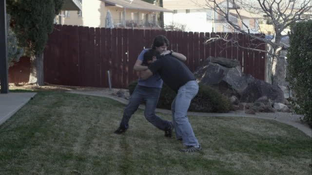 father and son wrestling iin the back yard as dad injures his lower back. - play fight stock videos and b-roll footage
