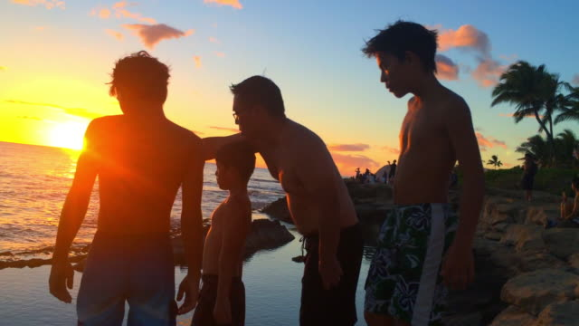 stockvideo's en b-roll-footage met father and sons at the beach during sunset - familie met drie kinderen
