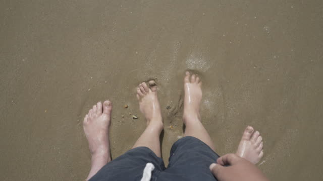 Father and sons feet in the water.