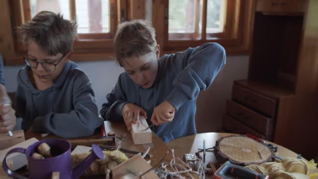 vidéos et rushes de père et fils apprenant le bois de découpage - sculpture production artistique