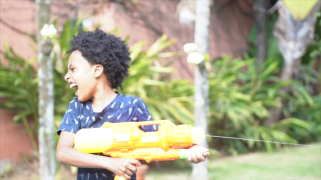 father and sons playing with squirt gun in backyard - water pistol stock videos & royalty-free footage