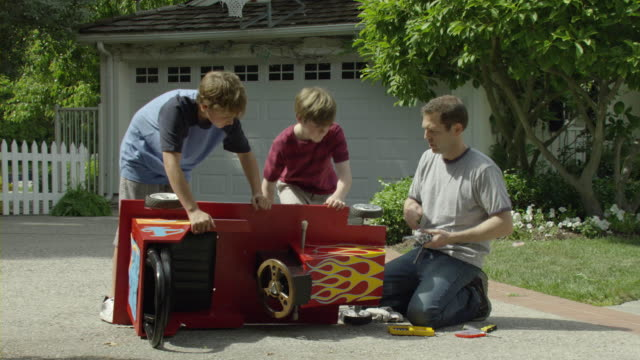 ms pan father and sons (10-11) repairing toy car in driveway, encino, california, usa - wrench stock videos & royalty-free footage