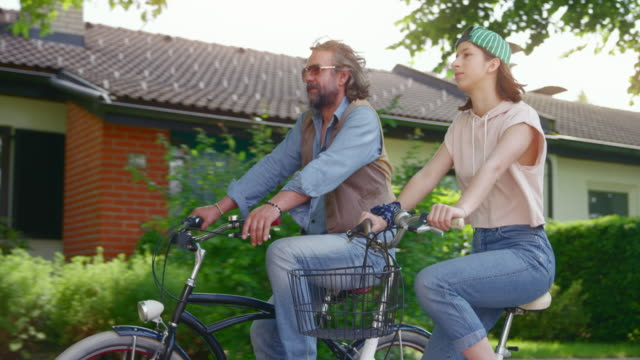 slo mo ts father and teenage daughter riding their bicycles down the sunny street - 18 19 years stock videos & royalty-free footage