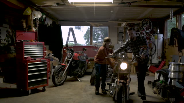 father and teenage son pushing motorbike in garage. - motorrad stock-videos und b-roll-filmmaterial