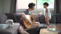Father and toddler boy playing guitar indoors in the living room at home.