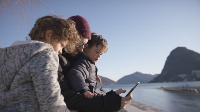 father and two children sit outdoors by lake looking at smartphone - wollmütze stock-videos und b-roll-filmmaterial