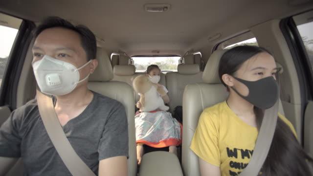 vidéos et rushes de père et deux filles avec le masque médical de visage dans le voyage de route de voiture sous l'éclosion de coronavirus - habitacle de voiture