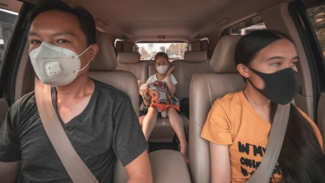 vídeos de stock e filmes b-roll de father and two daughter with surgical mask in the car road trip under coronavirus outbreak - interior de carro
