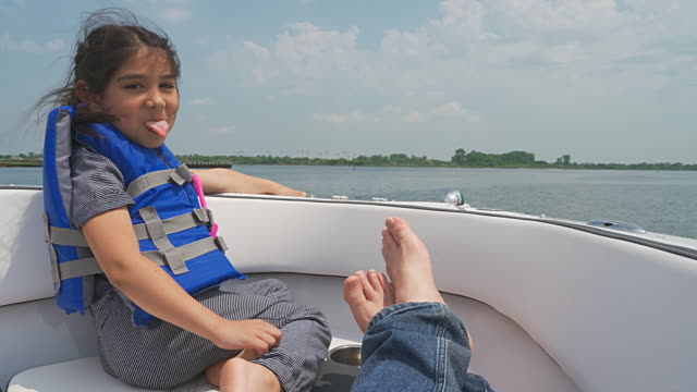 father and two daughters, sisters, riding motorboat in the sea. panoramic camera motion from the little girl to the older one, teenager. booth girls have fun and sticking tongues. - nautical vessel stock videos & royalty-free footage