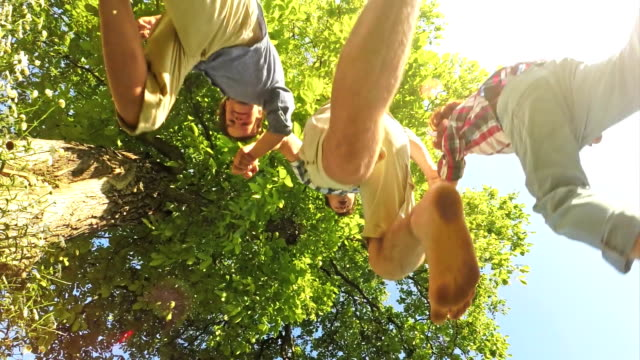 SLO MO Father and two sons jumping over the camera