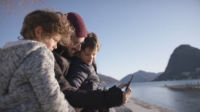 father and two sons looking at smartphone together - lake stock videos & royalty-free footage