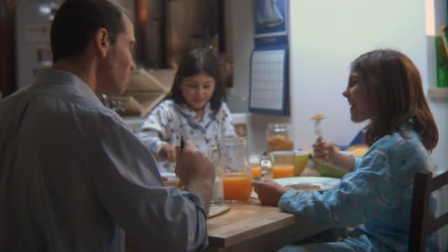 ms father and two young daughters eating breakfast at kitchen table/ rome, italy - bricco video stock e b–roll
