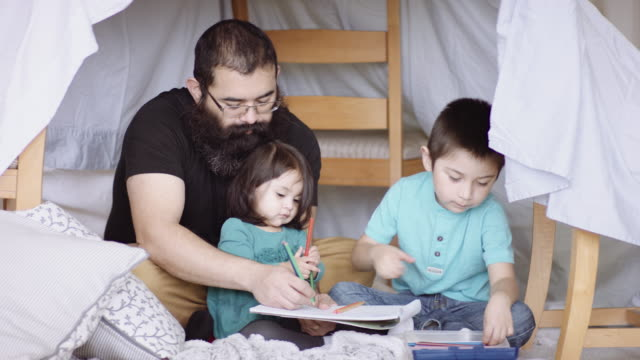 father and young children reading book in fort - fort stock videos & royalty-free footage