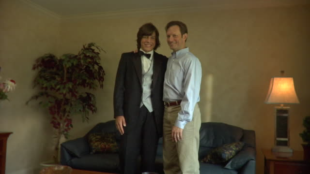 ms, father and young man in tuxedo in living room, portrait, edison, new jersey, usa - 腕をまわす点の映像素材/bロール