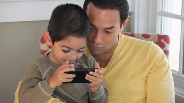 ms father and young son playing video game on smart phone / eastville, virginia, usa - leisure games stock videos & royalty-free footage