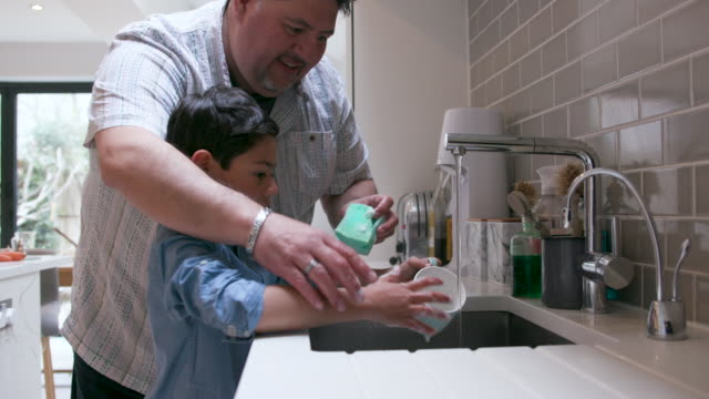 father and young son washing up together at the kitchen sink - chores stock videos & royalty-free footage