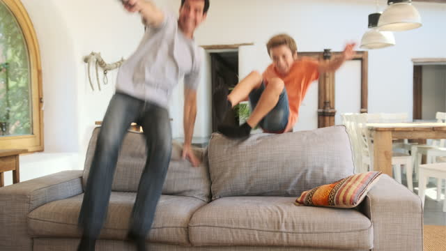father and young sonjumping over back of sofa - jumping stock videos & royalty-free footage