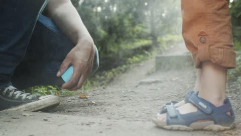 息子の足に虫けんを塗る父 - 虫除け点の映像素材/bロール