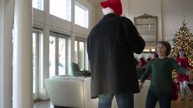 vidéos et rushes de father arriving home with presents at christmas - débarquement