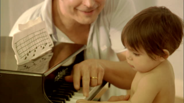 cu, td, tu, father assisting baby girl (9-12 months) playing toy piano - genderblend stock videos & royalty-free footage