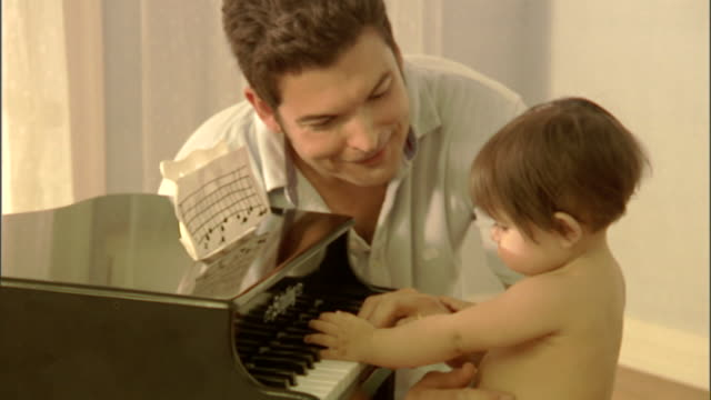 cu, father assisting baby girl (6-9 months) playing toy piano - genderblend stock videos & royalty-free footage