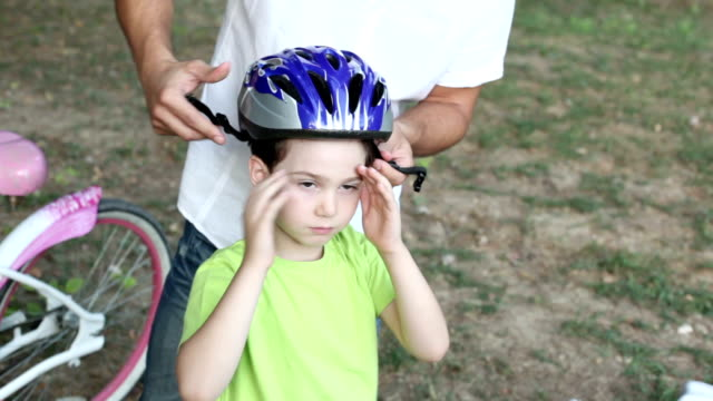 hd: father assisting child with cycling helmet. - helmet stock videos & royalty-free footage
