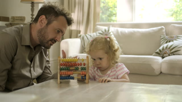 father assisting his daughter in counting abacus - abakus bildbanksvideor och videomaterial från bakom kulisserna