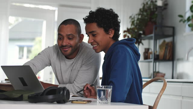 father assisting smiling boy in doing homework through laptop while sitting at dining table - son stock videos & royalty-free footage