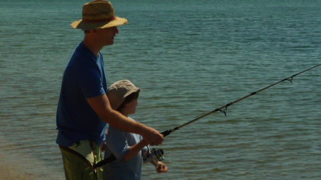 vídeos de stock, filmes e b-roll de ms, father assisting son (6-7) fishing in ocean, north truro, massachusetts, usa - usa