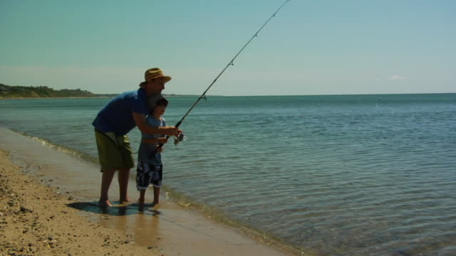 WS, Father assisting son (6-7) fishing in ocean, North Truro, Massachusetts, USA