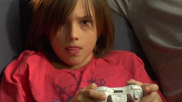vídeos de stock e filmes b-roll de cu, pan, father assisting son (8-9) playing video game - barba