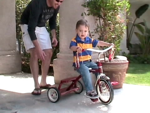 vídeos de stock e filmes b-roll de ms, father assisting son (2-3) riding tricycle in front of house, simi valley, california, usa - sapato