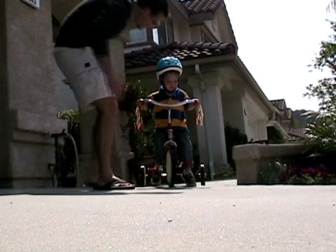 ms, ts, father assisting son (2-3) riding tricycle on street, simi valley, california, usa - tricycle stock videos & royalty-free footage