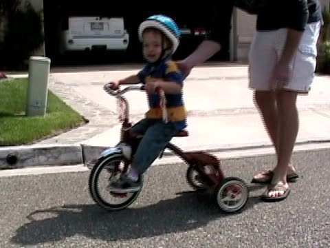 ms, father assisting son (2-3) riding tricycle on street, simi valley, california, usa - home movie stock videos & royalty-free footage