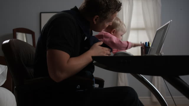 father at his desk with baby - see other clips from this shoot 1420 stock videos and b-roll footage