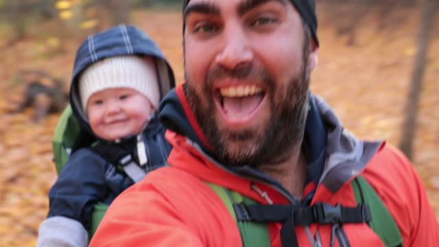 father backpacking hiking with baby in autumn forest - recreational pursuit stock videos & royalty-free footage