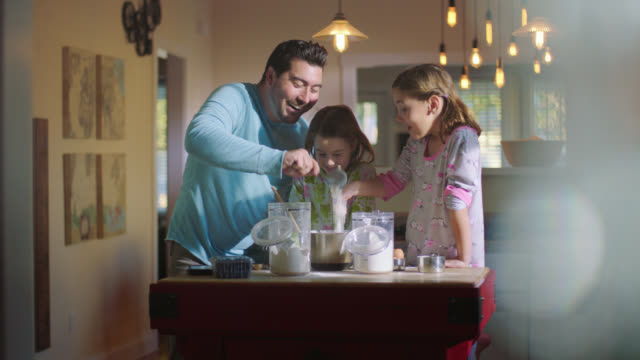 WS. Father bakes in the kitchen with his daughters, sifting flour into mixing bowl as kids stir batter.