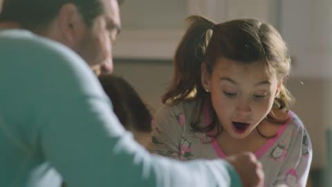 vídeos y material grabado en eventos de stock de ms. father bakes in the kitchen with his daughters, sifting flour into mixing bowl as kids stir pancake batter. - plato de comida